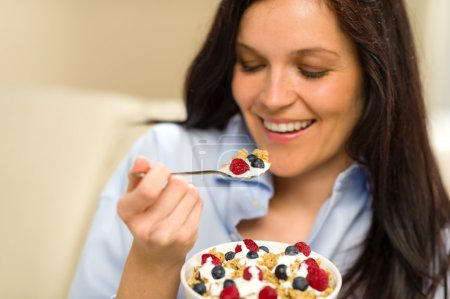 Relaxed woman eating cereal for breakfast