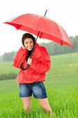 Happy young woman standing in the rain