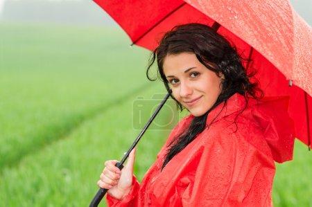 Smiling woman looking at camera during rainfall