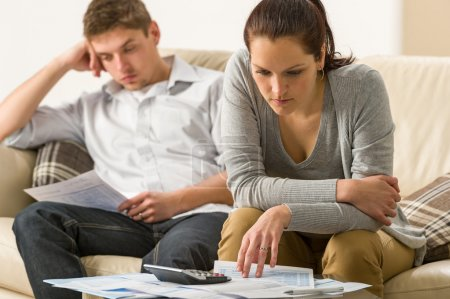Photo for Annoyed couple calculating their finances during recession - Royalty Free Image
