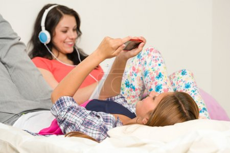 Teen girls relaxing on bed checking phone