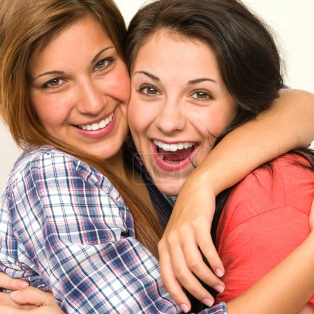 Caucasian sisters embracing, laughing at camera