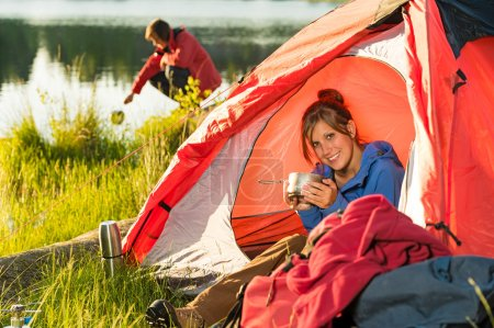 Photo for Camping girl sitting in tent drinking from pot - Royalty Free Image