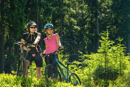 Mountain bikers resting in forest