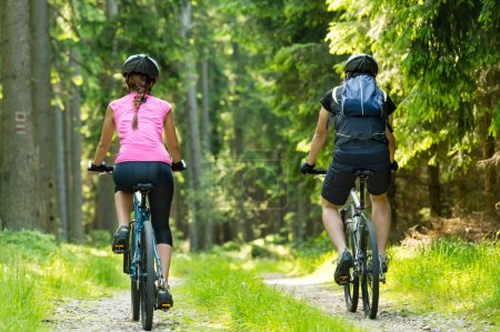 Photo for Bikers in forest cycling on track from behind - Royalty Free Image