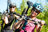 Sporty couple carrying their mountain bikes