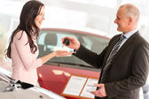 Salesman handing car keys to woman