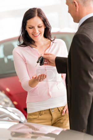 Woman receiving the keys of new car