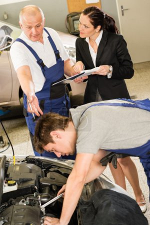 Upset customer showing papers to car mechanic