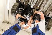 Auto mechanics working underneath a car