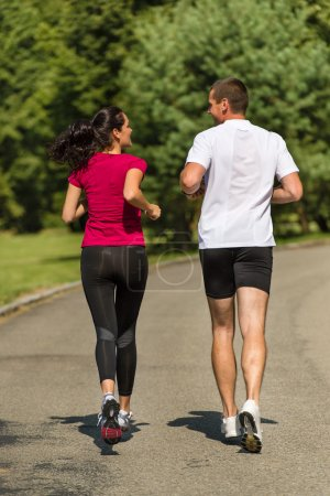 Rear view of couple friends jogging together