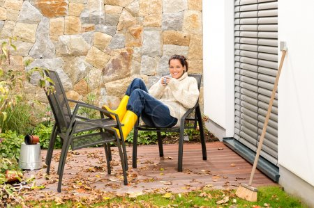 Happy woman relaxing autumn patio drinking tea