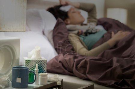 Photo pour Tissus, médicaments grippe et thé sur une femme malade de table de chevet - image libre de droit