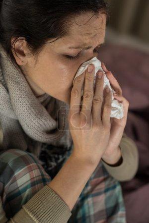 Portrait of woman sneezing into tissue