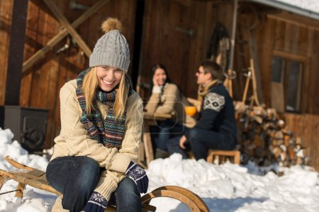 Young woman with friends snow winter cottage