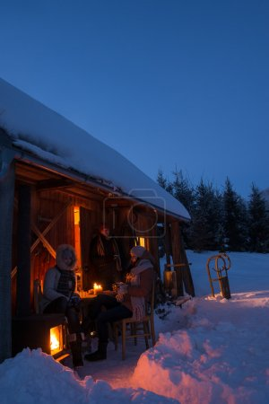 Sunset winter cottage friends enjoying evening