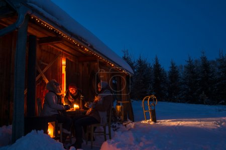 Evening winter cottage friends enjoy hot drinks