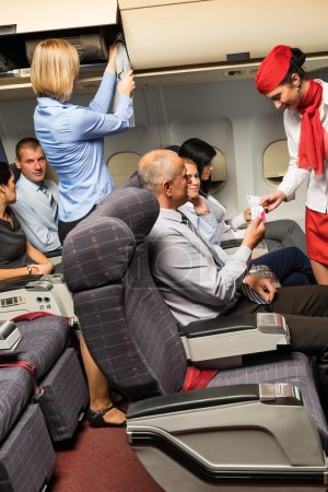 Flight attendant check passenger tickets cabin
