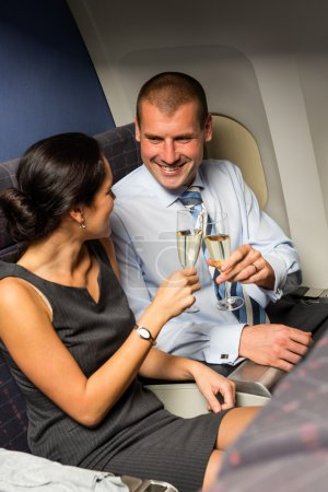 Smart couple travel by airplane toasting champagne