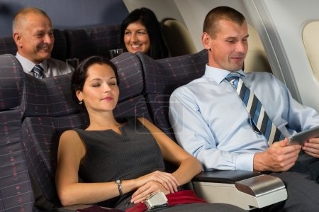 Photo for Airplane passengers relax during flight cabin sleep businesspeople - Royalty Free Image