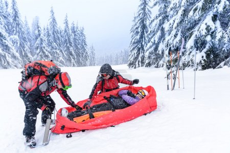 Ski patrol with rescue sled injured woman