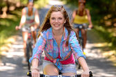 Teenage girl riding bike with friends