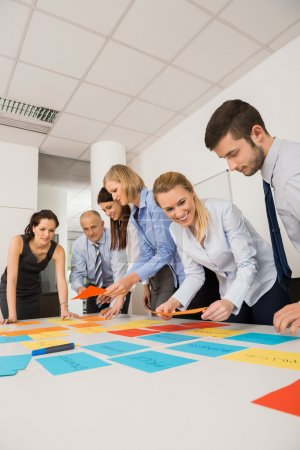 Photo for Business colleagues brainstorming with multicolored labels planning strategy in meeting - Royalty Free Image