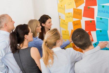 Photo pour Collègues d'affaires remue-méninges étiquettes multicolores collées sur le tableau blanc dans la réunion - image libre de droit
