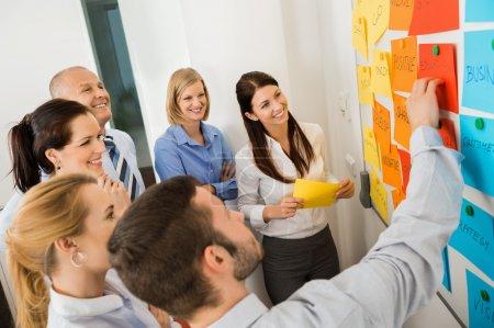 Photo pour Homme d'affaires expliquant les étiquettes sur le tableau blanc à ses collègues en réunion - image libre de droit