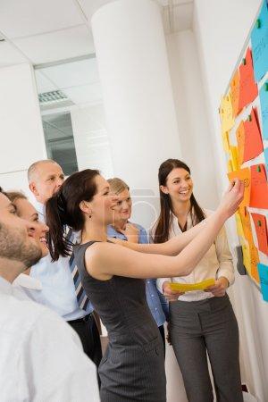 Geschäftsfrau klebt Etiketten auf Whiteboard
