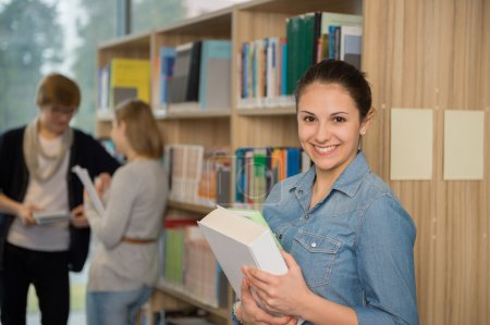Student holding books in university library