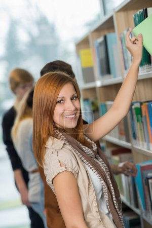 Student taking book from bookshelf in library