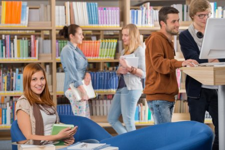 Photo for Smiling young student with friends discussing in background at library - Royalty Free Image