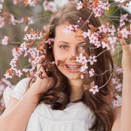 Girl holding blossoming tree branch