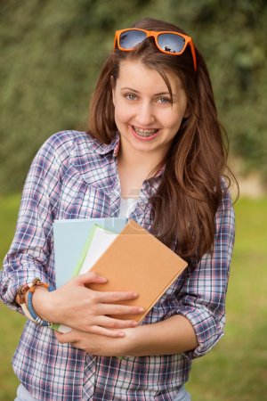 Student with braces holding books