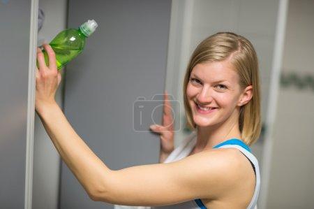 Woman putting bottle in locker