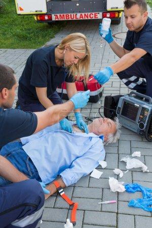 Paramedics examining man