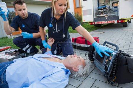 Paramedics checking pulse of man