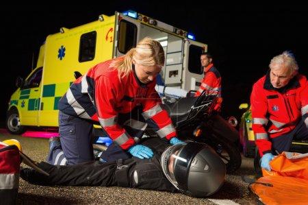 Paramedical team assisting injured driver