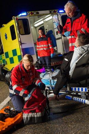 Paramedic team assisting injured driver