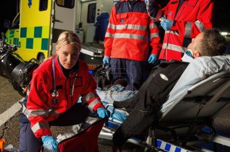 Paramedics assisting injured motorcycle driver