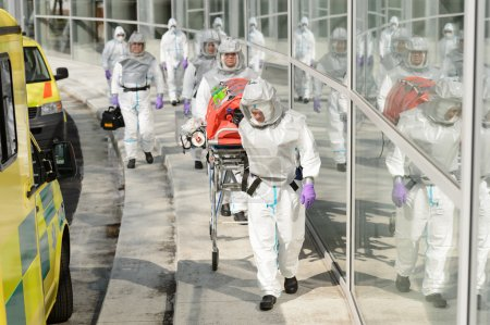 Photo for Biohazard team with stretcher wear protective uniform walking outside building - Royalty Free Image