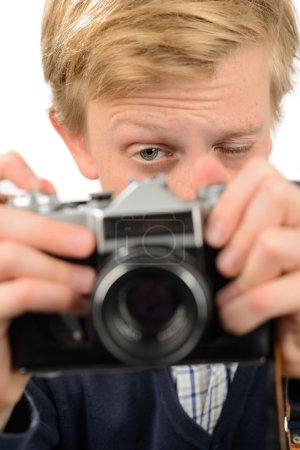Boy photographing through retro camera