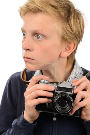 Shocked boy holding retro camera