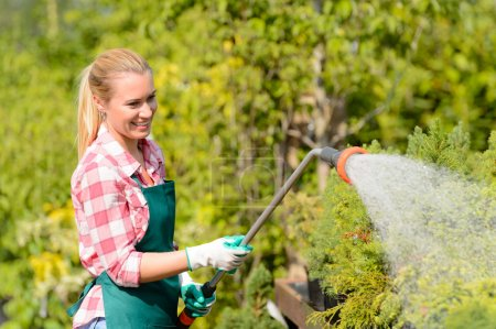 Woman watering plants with hose