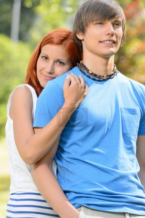Photo for Teenage girlfriend hugging her boyfriend from behind sunny park - Royalty Free Image