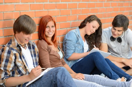 Photo pour Étudiants assis en rangée contre le mur de briques notes d'écriture - image libre de droit