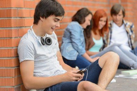 Photo pour Jeune homme étudiant traînant avec des amis de collège assis par terre - image libre de droit