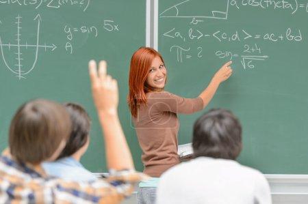 Photo pour Étudiant de leçon de mathématiques écrire sur l'ardoise verte en regardant ses camarades de classe - image libre de droit