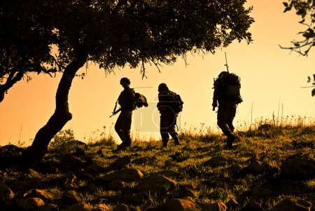 Three soldiers patrolling during sunset